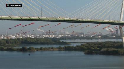 Activistas de Greenpeace descienden en rápel por el puente de Houston y detienen embarques de petróleo